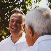 Pflegekraft und älterer Herr lachen gemeinsam