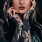 Eine Frau mit vielen Tatoos und einem Nasenpiercing