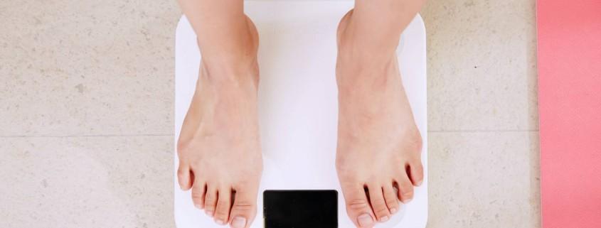 Frau oder Mann steht auf einer Waage - amn sieht nur die Füße